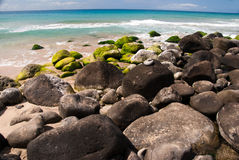Green Rocks on a Tropical Beach. Green rocks on Hanakapi'ai beach on the island of Kauai, Hawaii Stock Images