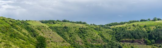 Green rocky hill. Eastern Europe in summer. Several rural houses on both sides of the hill royalty free stock photo