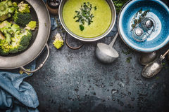 Green Romanesco and broccoli soup with cooking ingredients, ladle , bowls and spoons on dark rustic background, top view, border. Healthy and vegetarian food Royalty Free Stock Photos