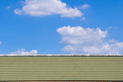 Green roof and blue sky. Green roof texture tile and blue sky with cloud in background Royalty Free Stock Photos