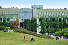 The green roof of modern library. Warshaw, Poland - June 8, 2015: The green roof of modern library of Warsaw University. Two young people sitting on the grass Royalty Free Stock Photo