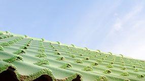 Green roof tile pattern over blue sky Royalty Free Stock Images