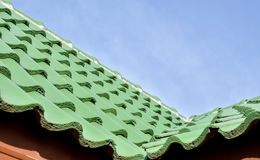 Green roof tile pattern over blue sky Royalty Free Stock Photos