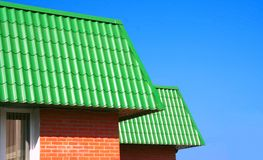 Green roofs. Of two small brick small houses in a bright sunny day Stock Photos