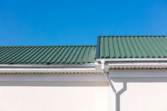 Green rooftop of newly built house white metal gutter pipes and downspout on blue sky background. Green rooftop of newly built house and white metal gutter pipes royalty free stock photography