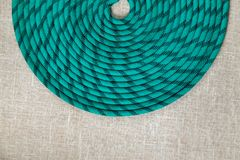 Green rope for mountaineering or sailing in irregularly wound ring. On textured fabric background Stock Images