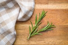 Green rosemary branch. Green rosemary branch with napkin on wooden table Royalty Free Stock Photography