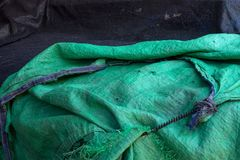 A green rough burlap awning lies carelessly against a black background. Green rough burlap awning lies carelessly against a black background Royalty Free Stock Image