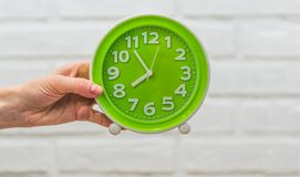 Green round clock in a female hand. On a white background Royalty Free Stock Images