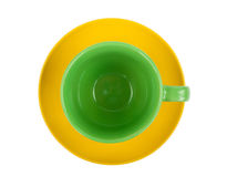 Green round empty tea cup on a yellow saucer Royalty Free Stock Photos