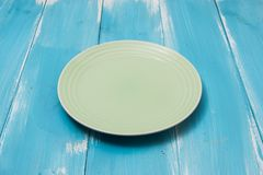Green Round plate on blue wooden table with perspective. Side view Stock Images