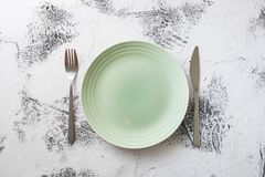 Green Plate on white wooden background with utensils Royalty Free Stock Image
