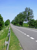 Green route. Perspective of road with white lines through green field with the trees under blue sky Stock Photos