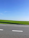 Green route - close up. Close up of road with white lines. The green field in the background under blue sky Royalty Free Stock Photography