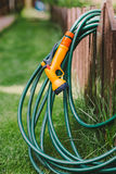 A green rubber garden hose with nozzle. Outdoor stock photos