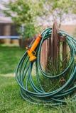 A green rubber garden hose with nozzle. Outdoor royalty free stock photos