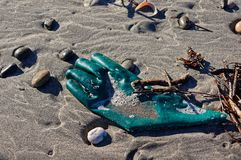 Green rubber glove washed up on a beach. On New Zealand`s west coast royalty free stock images