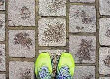 Green running shoes on dirty concrete brick top view. Sport concept Royalty Free Stock Photo