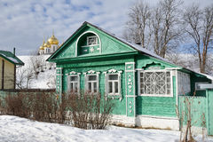 Green Russian Wooden House on Kropotkinskaya Street in Dmitrov. Traditional Russian wooden house with carved windows in historical center of Dmitrov city. Behind Stock Images