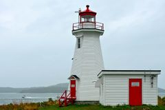 Green`s Point Lighthouse. A boat speeds past the Green`s Point Lighthouse on a foggy, overcast day. Also known as the L`Etete Passage Light. L`Etete, New royalty free stock photography