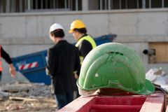 Green safety hardhat on foreground. Two construction workers on out of focused background. Green safety helmet on foreground. Two back turned construction Stock Photos