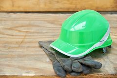 Green safety helmet and gauntlet cloves on a woode background.  Stock Image