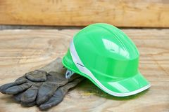 Green safety helmet and gauntlet cloves on a woode background.  Royalty Free Stock Photos