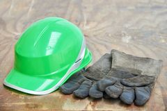 Green safety helmet and gauntlet cloves on a woode background Royalty Free Stock Image