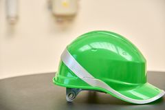 Green safety helmet on a table Royalty Free Stock Photos