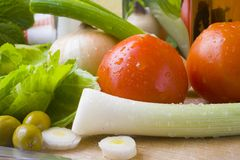Green salad. Preparing a green salad on a wooden table with knife royalty free stock images