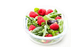 Green salad with arugula and berries and pine nuts on white Royalty Free Stock Photo