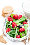 Green salad with arugula and berries and pine nuts on white tab Stock Photo