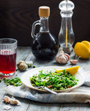 Green salad with arugula, cheese, almonds, lemon, garlic royalty free stock photos
