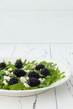 Green salad with arugula, feta cheese and berries. Royalty Free Stock Photography