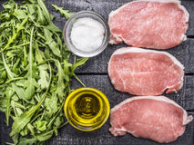Green salad of arugula with oil and salt with raw pork steak wooden rustic background top view close up. Green salad of arugula with oil and salt with raw pork Royalty Free Stock Photo