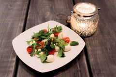 Green Salad with Arugula, Tomatoes, Cheese Mozzarella Balls on P Royalty Free Stock Image