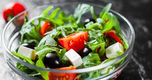 Green salad with arugula, tomatoes, cheese, pepper and olive in glass bowl on dark background. Fresh green salad with arugula, tomatoes, cheese, pepper and olive royalty free stock image