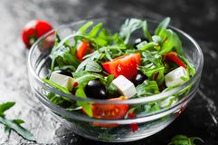 Green salad with arugula, tomatoes, cheese, pepper and olive in glass bowl on dark background. Fresh green salad with arugula, tomatoes, cheese, pepper and olive stock image