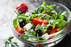 Green salad with arugula, tomatoes, cheese, pepper and olive in glass bowl on dark background. Fresh green salad with arugula, tomatoes, cheese, pepper and olive stock photography
