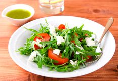 Green salad with arugula, tomatoes and feta cheese. Green salad with arugula, tomato and feta cheese. Italian cuisine royalty free stock photos