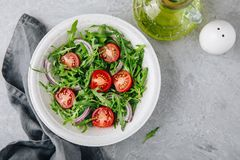 Green salad arugula with tomatoes and red onion in bowl Royalty Free Stock Photos