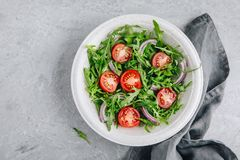 Green salad arugula with tomatoes and red onion in bowl Royalty Free Stock Photo