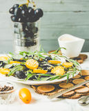 Green salad with arugula, yellow tomatoes, olives, grapes, sesam. Fresh green salad with arugula, yellow tomatoes, olives, grapes and sesame,healthy lifestyle Royalty Free Stock Photography