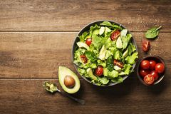 Salad with avocado and tomato. Green salad with avocado and fresh vegetables on wooden background Stock Photos