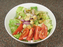 Green salad in a bowl. Green salad with tomato, lettuce, onion, crouton and salad dressing in a bowl Royalty Free Stock Photo