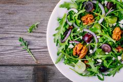 Green salad bowl with arugula, walnuts, goat cheese, red onion and grapes stock image