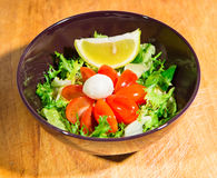 Green salad with cherry tomatoes and mozzarella. Over wood background Royalty Free Stock Images