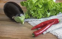 Green salad, eggplant and chili on a wooden table. On a wooden table are vegetables: eggplant, chili and green salad in a small red container stock photo