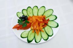 Green salad and fresh cucumbers in a bowl. Table setting stock image