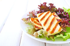 Green salad with fried halloumi cheese in a white plate Royalty Free Stock Image